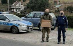 Na zdjęciu dzielnicowy z Komisariatu II Policji w Jeleniej Górze wspólnie z żołnierzem z Jednostki Wojskowej w Świętoszowie roznoszą paczki seniorom. W tle radiowóz.